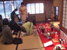 阿部肥先生の人形とこどもたちが生けた花雛を見入る様子